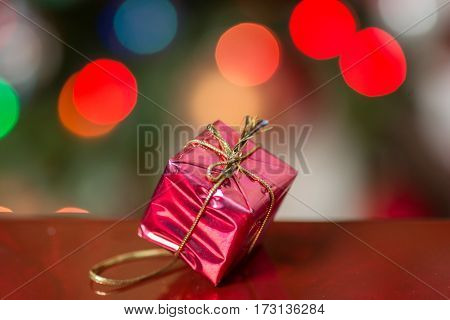 Small Present Wrapped in Red with Bokeh Background