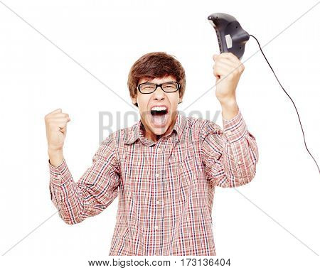 Young hispanic man wearing glasses and checkered shirt, standing and happy screaming celebrating win with raised in one hand game console controller isolated on white background - video games concept