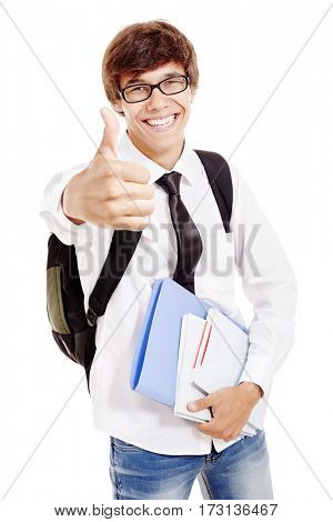 Young man with backpack wearing glasses, blue jeans, white shirt and black tie, holding books and folder in his hand, smiling and showing thumb up isolated on white background - education concept