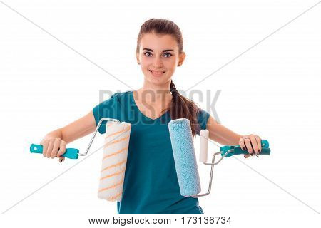 studio portrait of young cheerful brunette girl in uniform makes renavation with paint roller in hands smiling on camera isolated on white