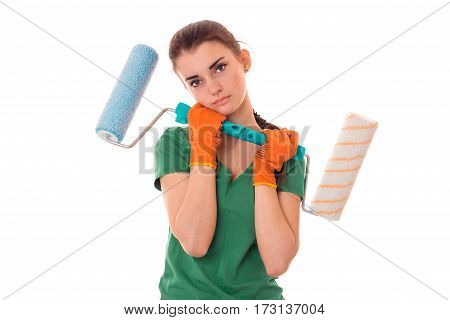 studio portrait of young tired brunette girl in uniform makes renavation with paint roller in hands isolated on white