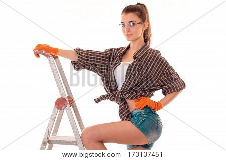 studio portrait of young beautiful brunette girl in uniform and glasses makes renavation on ladder and smiling on camera isolated on white