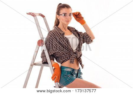 studio portrait of young sexy brunette girl in uniform and glasses makes renavation on ladder and looking at the camera isolated on white