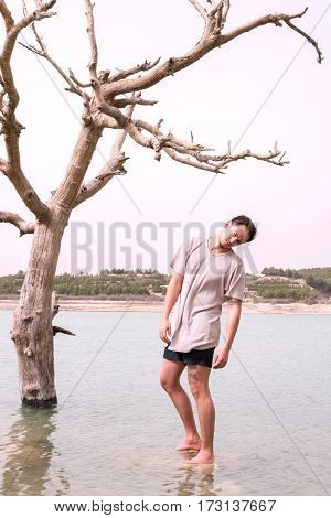 conceptual image of climate change. young man mimics the dying tree as if there was a rope hanging from the branches in a lake that has been floodedfilter added blank sky in background for copy space