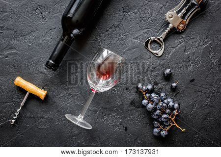 glass bottle of red wine with wineglass on dark texture background top view
