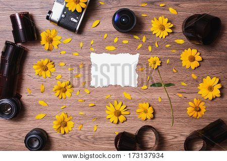 Old vintage camera and lens lying on the wooden background. Film and three lenses lie on a table. Place for design. Blank white sheet of paper. Yellow flowers and petals. A flower with a green stem. Manual lens