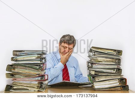 Man Studies Folder With Files At His Desk