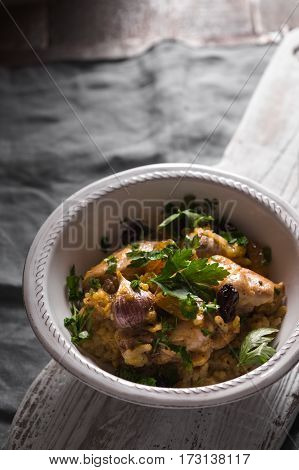 Pilaf with rice, chicken and raisins in a ceramic bowl vertical