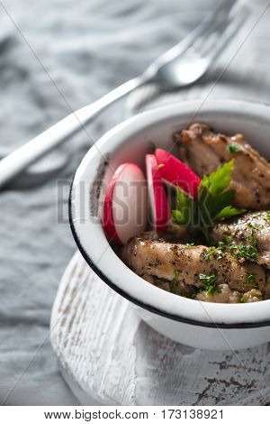 Pilaf with chicken in a metal bowl and radishes vertical