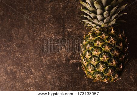 Ripe pineapple lying on a dark marble table. Delicious fruit. Healthy eating.