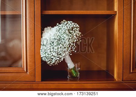 wedding bouquet of white gypsophila and hydrangea white ribbon in vintage sideboard