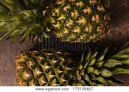 Diet of fruits.. Two ripe pineapple lying on a dark marble table. Delicious fruit. Healthy eating. Fruits on the table. Fruits on a wooden background.
