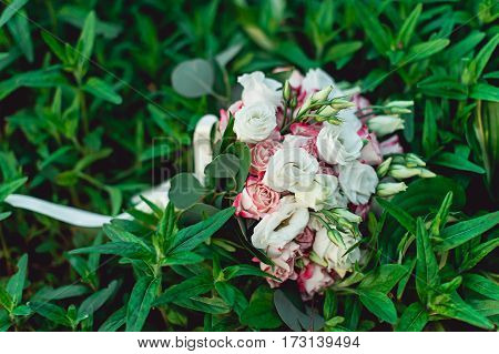 wedding bouquet of white and biege roses in brides hands