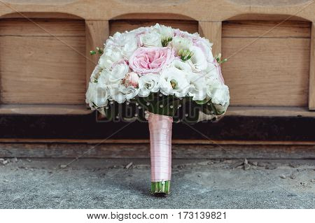 wedding bouquet of white and biege roses on the floor