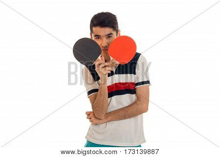 portrait of attractivee sportsman with rackets in his hands and uniform practicing table tennis on camera isolated on white