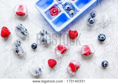 fresh blueberry and raspberry in ice tray on gray stone background top view