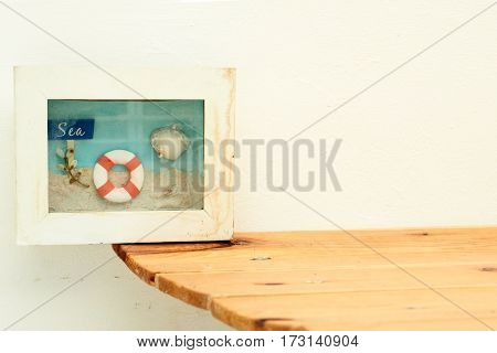 Background concept decor is box frame white color inside is small beach modle has sea word sign shell lifebuoy and sand on wood table and cement wall.