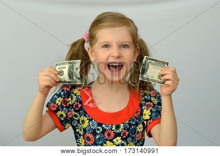 Baby girl holds in hands a torn banknote ,dollar ,banking crisis.