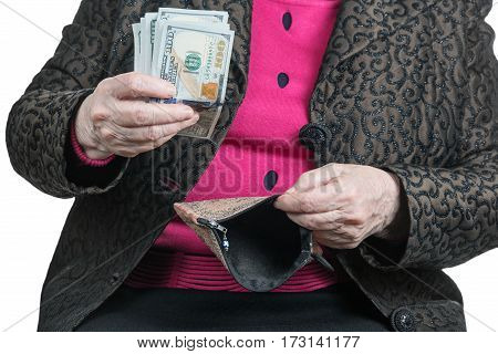 Senile hands holding dollars pack and empty purse