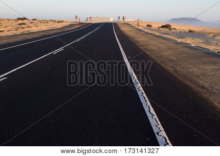 Road rough texture. Black asphalt with white line middle. Divided way. Sunrise, Spain, Fuerteventura