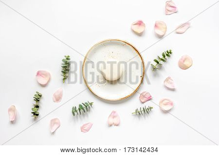 woman breakfast with rose petals and macaroons in soft light on white table background top view