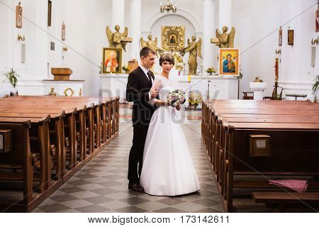 Groom and bride in a white dress in the church. Wedding ceremony. Happy family