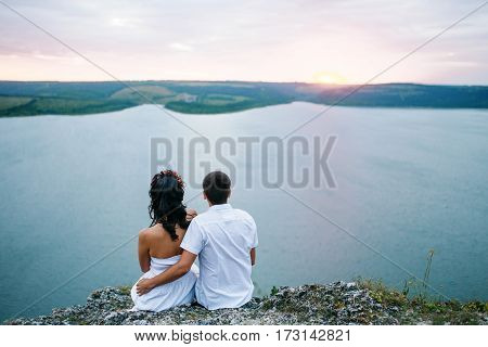 Back View Of Loved Couple In Love Sitting At Amazing Landscape Against Cliff Rocks.