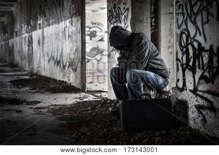 Hobo man in old abandoned ruin with suitcase