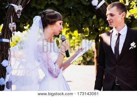 Groom and bride in white dress on background of the arch. Wedding ceremony. Happy family