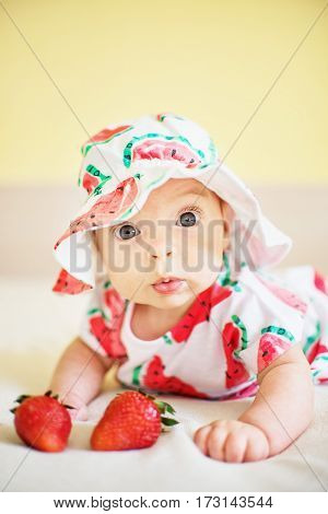 A cute baby girl dressed in a hat and a dress with water melon print with tow strawberries