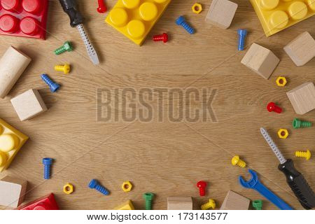 Boys toys frame background. Colorful toy tools, construction blocks and cubes on wooden table. Top view. Flat lay.