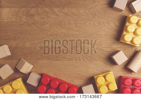 Toys background with copy space for text. Bright construction blocks and cubes on wooden background as frame. Top view. Flat lay