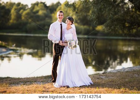 Happy groom and bride in white dress on background of water. Happy couple. Wedding photography. A happy family. A happy family. Happy people on nature background