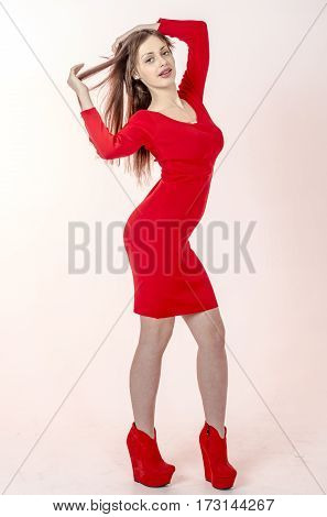 Young go go girl with a beautiful figure in a trendy red dress in skin-tight jacket and red high heels and platform  dressed for a party
