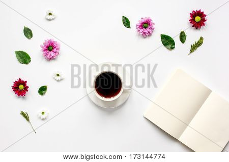 Froral flat lay with cup of coffee and craft notepaper on white background top view mockup