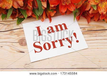 I am sorry message A bouquet of orange lilies on weathered wood with a greeting card with text I am Sorry