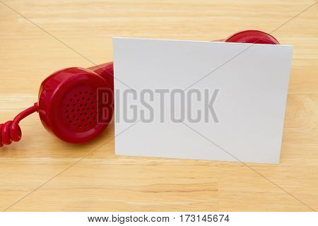 A retro red phone with greeting card on a desk with copy space for your message