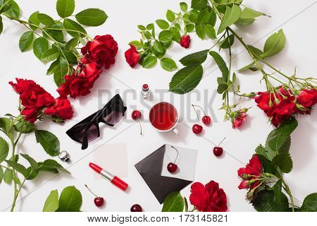Frame of red beautiful roses with green leaves lady lipstick red tea black glasses a ring with a black stone envelope ripe cherries and a leaf of paper lie on a white background. Flat lay roses. Frame of roses