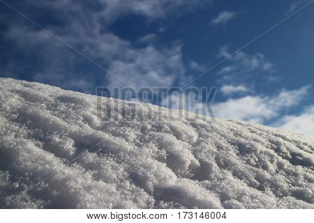 mountain covered with white fluffy snow against the blue sky low angle view