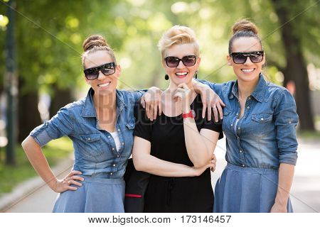 portrait of three young beautiful woman with sunglasses. twin sisters enjoy with a girlfriend in a sunny day in the park
