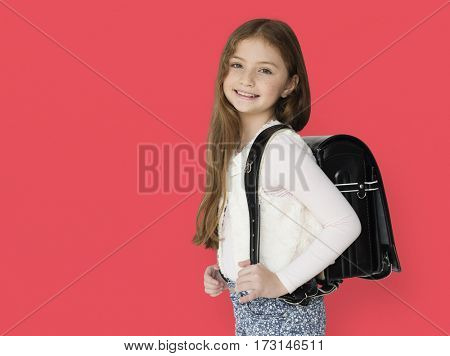 Young freckled girl carrying a backpack smiling portrait