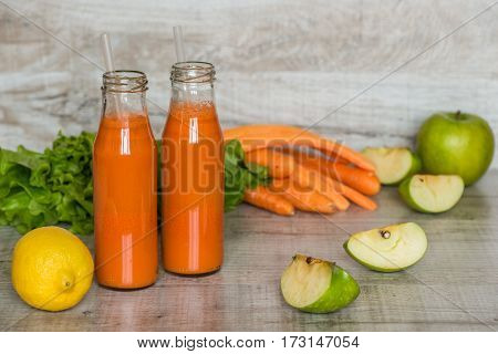 Fresh carrot juice in bottles on a grey wooden table.