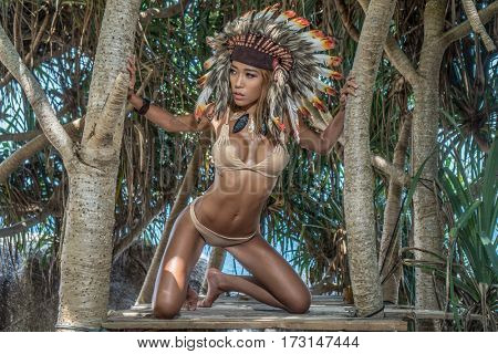 Sensual Native American Indian looking woman wearing nude bikini and indian feather hat looking aside while sitting on her knees between tropical trees on sunny summer day