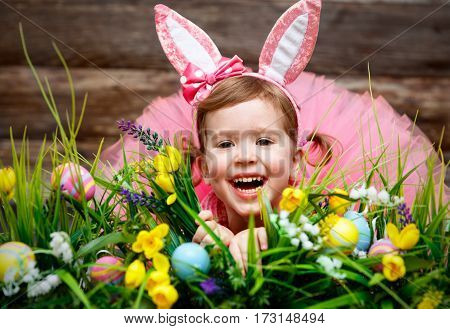 happy fanny child girl in easter bunny costume with eggs