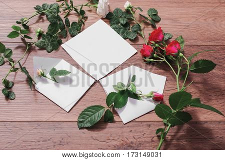 Envelope with flowers. A congratulation in envelope. Open envelopes frame of red and white roses and red hearts on wooden background. Greeting card. Conceptual photography. Wedding invitation card. Valentine day. Flat lay top view copyspace mock up