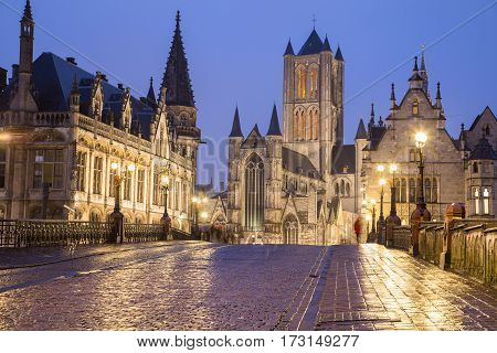 A view towards Saint Nicholas' Church in Ghent City Center at dusk. A cobbled road can be seen leading towards the landmark.