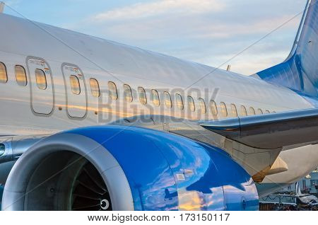 Airplane portholes, engine, tail. At sunset at the airport