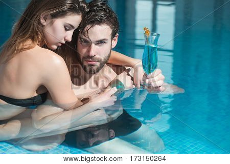 wet couple of pretty woman or sexy girl and handsome bearded man or guy with muscular body in swimming pool with blue water holds cocktail glass copy space