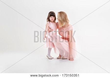 blonde mom and sweet little daughter in pink dresses princesses hugging and laughing on gray background. family