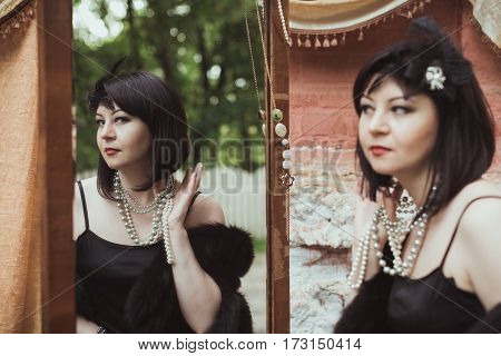 Portrait of a woman in retro style, looking in the mirror and holding a necklace
